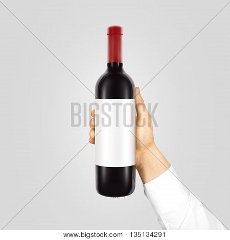 Blank white label mockup on black bottle of red wine in hand isolated. Alcohol bottle mock up presentation ready for logo design. Full drink bottle template with empty sticker. Clear tag vine bottle.