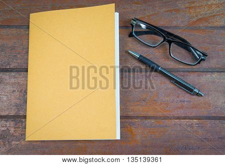 overhead notebook with pen and glasses on a wooden background
