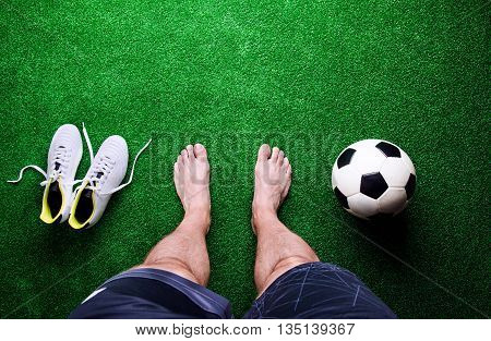 Barefoot Football Player Against Green Grass, Studio Shot