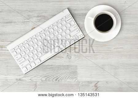 Workplace with cup of coffee and keyboard on wooden surface in top view. Workplace of office man or information technology specialist. Office stuff. Readiness for the new. Beginning of something new. First work day. Uplifting mood. Coffee break.