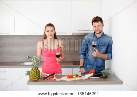 Young Couple In Kitchen With Wine.
