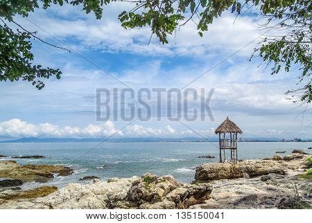 Expansive ocean view from rocky beach with palapa lifeguard shack and blue sky with puffy white clouds.