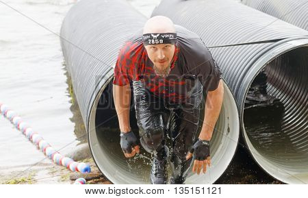 STOCKHOLM SWEDEN - MAY 14 2016: Man coming out from a tube obstacle in the obstacle race Tough Viking Event in Sweden May 14 2016