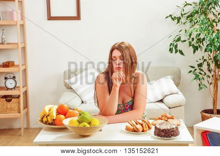 Portrait of beautiful fat woman sitting at table full of different foods: unhealthy and healthy ones at home.