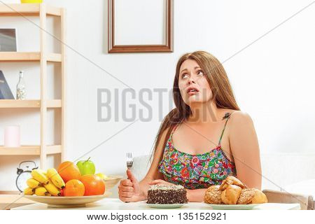 Portrait of fat woman on diet sitting at table with spoon in her hand and thinking whether to eat sweety cake or not at home.
