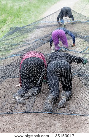 STOCKHOLM SWEDEN - MAY 14 2016: Rear view of a group of women crawl under a net obstacle in the obstacle race Tough Viking Event in Sweden May 14 2016