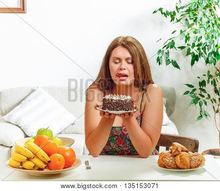 Portrait of fat woman holding sweety cake in front of her while sitting at table at home. Beautiful lady on diet. Diet concept.