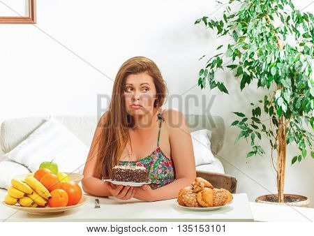 Portrait of beautiful fat woman on diet sitting at table at home. Sad pretty woman looking away and thinking whether to eat it or not.