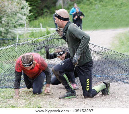 STOCKHOLM SWEDEN - MAY 14 2016: Group of women and men crawling under a net obstacle in the obstacle race Tough Viking Event in Sweden May 14 2016