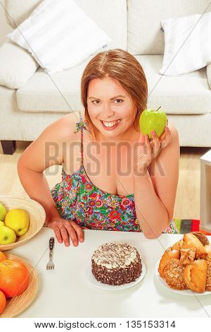 Top view of beautiful fat woman on diet sitting at table at home. Toothy smiling lady holding green apple in front of her.