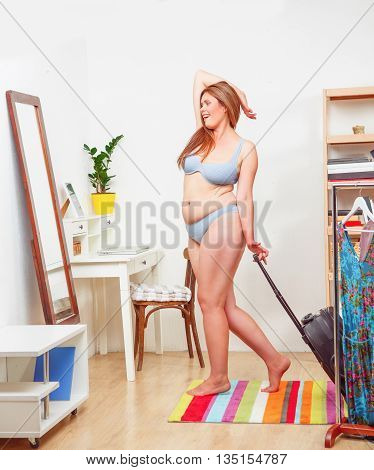 Portrait of fat woman in underwear or lingerie posing in full length in front of mirror. Lady with luggage or suitcase at home.