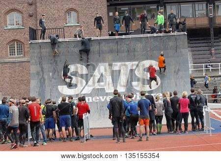 STOCKHOLM SWEDEN - MAY 14 2016: Group of men and woman waiting to climb the rampage obstacle in the obstacle race Tough Viking Event in Sweden May 14 2016
