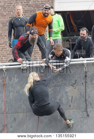 STOCKHOLM SWEDEN - MAY 14 2016: Woman climbing the rampage obstacle hanging in rope and beeing helped in the obstacle race Tough Viking Event in Sweden May 14 2016