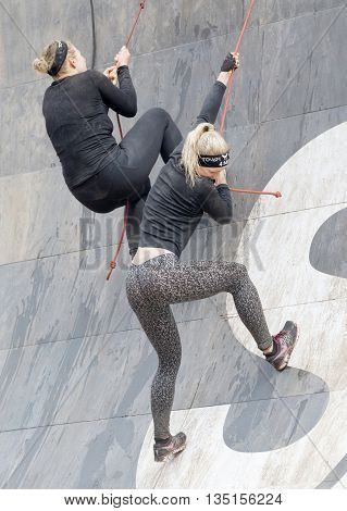 STOCKHOLM SWEDEN - MAY 14 2016: Two woman climbing the rampage obstacle hanging in rope in the obstacle race Tough Viking Event in Sweden May 14 2016
