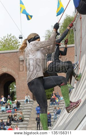 STOCKHOLM SWEDEN - MAY 14 2016: Group of men and woman climbing the rampage hanging in rope obstacle in the obstacle race Tough Viking Event in Sweden May 14 2016