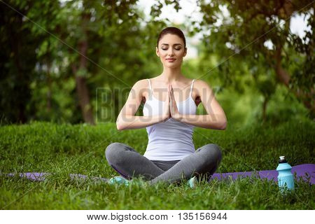 Peaceful young woman is doing yoga in the nature. She is sitting and joining her hands together. Her eyes are closed with enjoyment