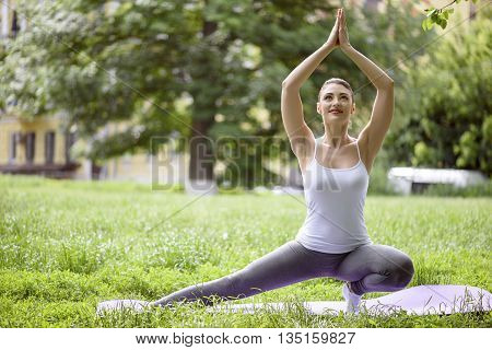Cheerful fit woman is doing yoga with enjoyment in park. She is kneeling and stretching leg sideways. Girl is looking up and smiling