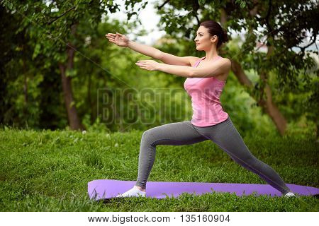 Healthy young woman is doing yoga in the nature. She is standing and posing. Athlete is looking forward with joy