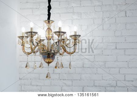 Beautiful glass chandelier against a white wall from a brick