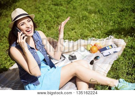 Cheerful young woman is talking on mobile phone and smiling. She is sitting in the nature and relaxing
