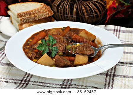 Homemade beef stew with carrots beef potatoes peas and a red sauce. Selective focus on spoon.