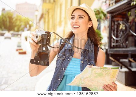 Joyful female tourist is photographing architecture of town. She is holding map and camera. Woman is standing and laughing
