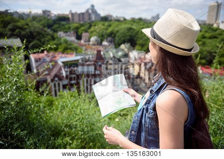 Pretty young woman is traveling to city. She is standing and enjoying the scenery. Girl is holding a guide map