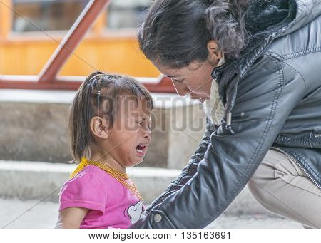 ALAUSI, ECUADOR, OCTOBER - 2015 - Closeup photo of young mother comforting her daughter crying.