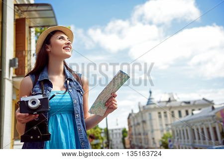 Happy young tourist is traveling across the city. She is looking around with admiration and smiling. Woman is holding camera and map