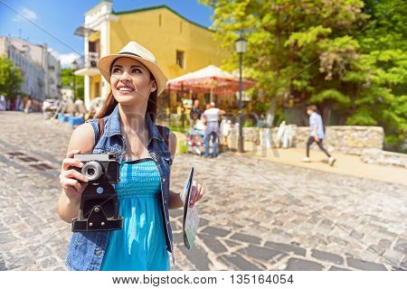 Cheerful young woman is making travel across town. She is looking aside with interest and smiling. Girl is walking and taking shots