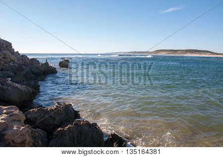 KALBARRI,WA,AUSTRALIA-APRIL 21,2016: Person fishing by the Indian Ocean and Murchison River river mouth point in Kalbarri, Western Australia with a rocky bank under clear skies.