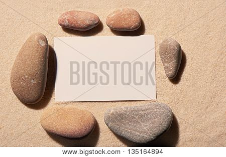 Rectangular Frame Of Sea Stones With White Visit Card On Sand