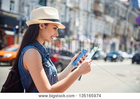 Pretty young woman is searching for place of destination. She is reading a map and using a mobile phone. Tourist is standing and smiling