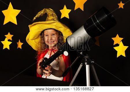 Happy five years old girl in sky gazer costume with a telescope at a dark starry background