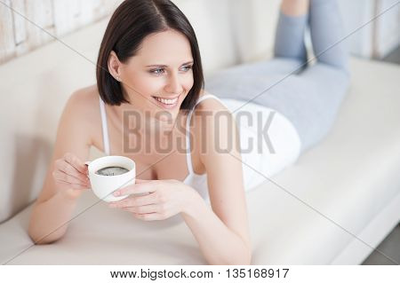 Enjoying weekend. Top view of lying woman reading book relaxing at home with cup of tea