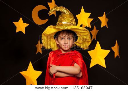 Five years old boy in sky watcher costume among big yellow paper stars and moon