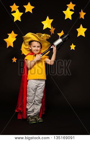 Full length photo of boy playing sky watcher with a telescope, standing against black background with paper stars above