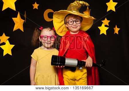 Two kids, boy and girl in stargazers costumes and bright glasses with a telescope, against black background with paper stars and moon