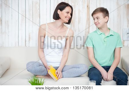Weekend together. Mother and her aduld son sitting on couch and looking at each other, smiling