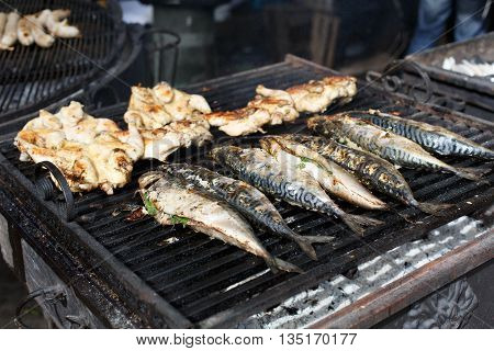 Plenty of chicken tabaka and mackerel fish grilled at barbecue. Mackerel and whole chicken bbq outdoors at picnic, party. Street food, meat and fish grill takeaway at grill grate