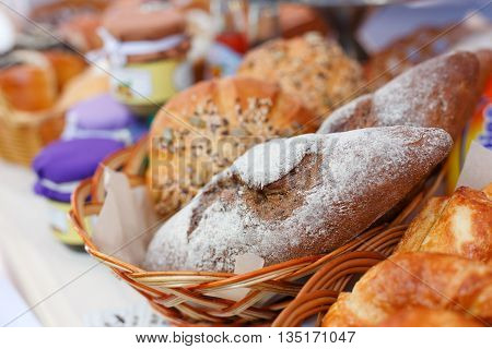 Healthy organic rye and white wheat homemade bread loafs with sesame in basket outdoors for sale. Country fair, tasty fresh bread loafs. Crispy buns. Whole grain bread