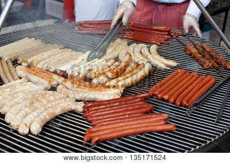 Sausage party. Chef cooking at barbecue big grill outdoors. Cookout bbq food. Roasted pork bratwurst german sausages, white polish kielbasa. Meat grilled meal. Street food, fast food. Tasty sausages.