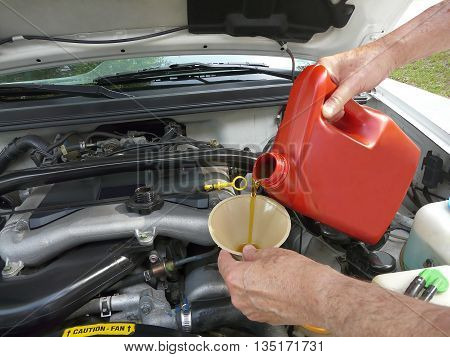 Male adding oil with a funnel to a white car after an oil change. Dipstick and cap are nearby.