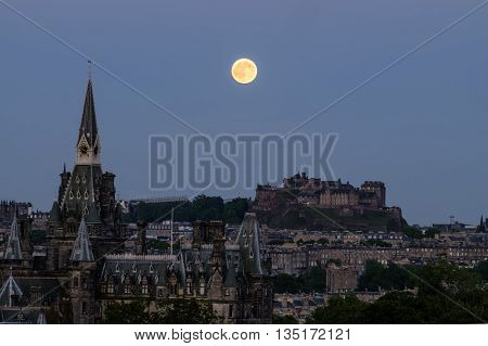 Strawberry moon on summer solstice over Edinburgh Castle Scotland