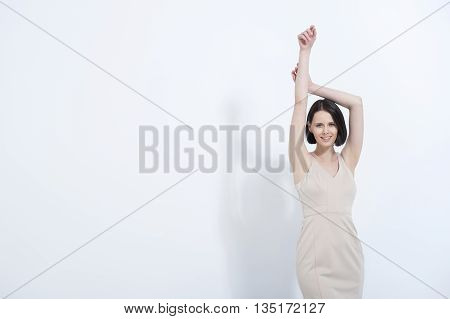 Ready to take on day. Beautiful brunette female in summer cream dress, isolated on white background
