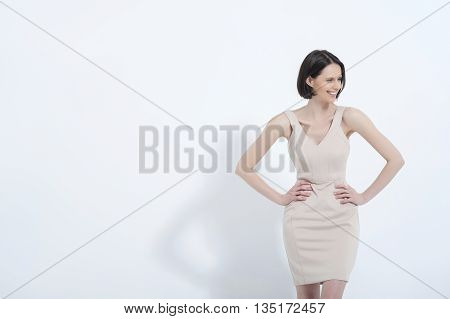 She owns that dress. Waist up studio shot of attractive woman in cream dress, isolated on white background