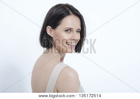 Playful wink. Studio shot of attractive young woman winking against white background