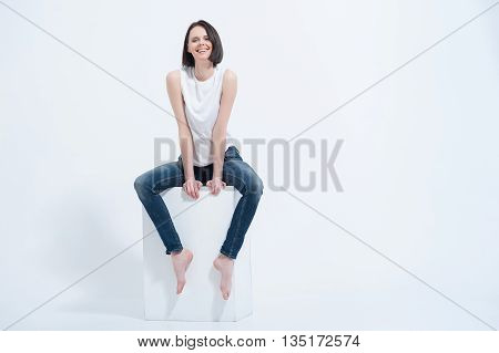 Looking and feeling great today. Pretty lady sitting on white cube in studio on white background
