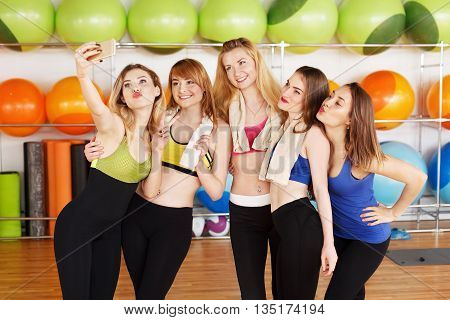 Making selfie. Group of girls in fitness class at the break look at cell phone show duck face. Girls do selfie after fitness training. Girl friendship, happiness, modern life, young people concept.