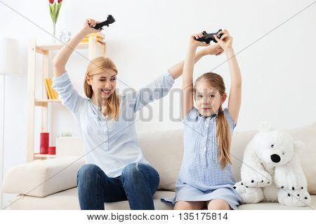 I won again. Happy mother and daughter playing video games, enjoying victory